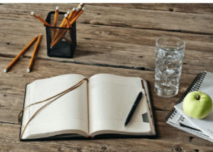 journal with a glass of water and an apple close by