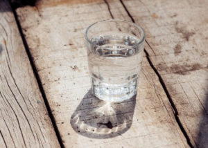 Image of a glass of water sitting in the sunlight.