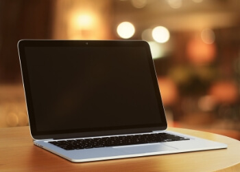 photo of a laptop computer with blurry cheerful lights in the background